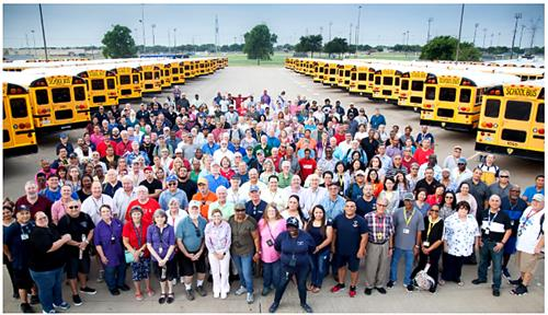 large group of transportation employees with many parked buses