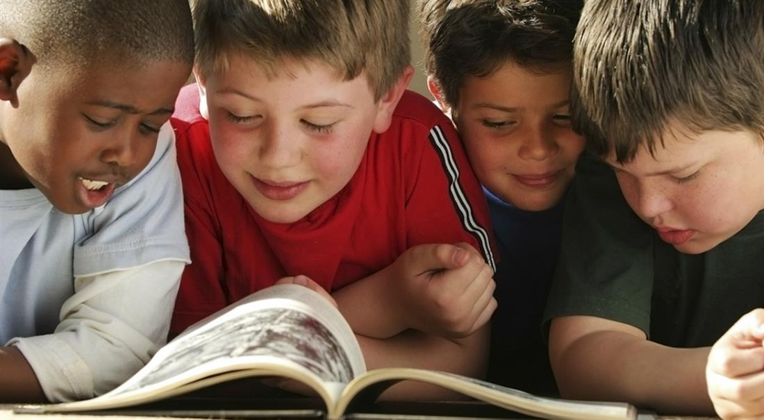 Four boys reading a book together.