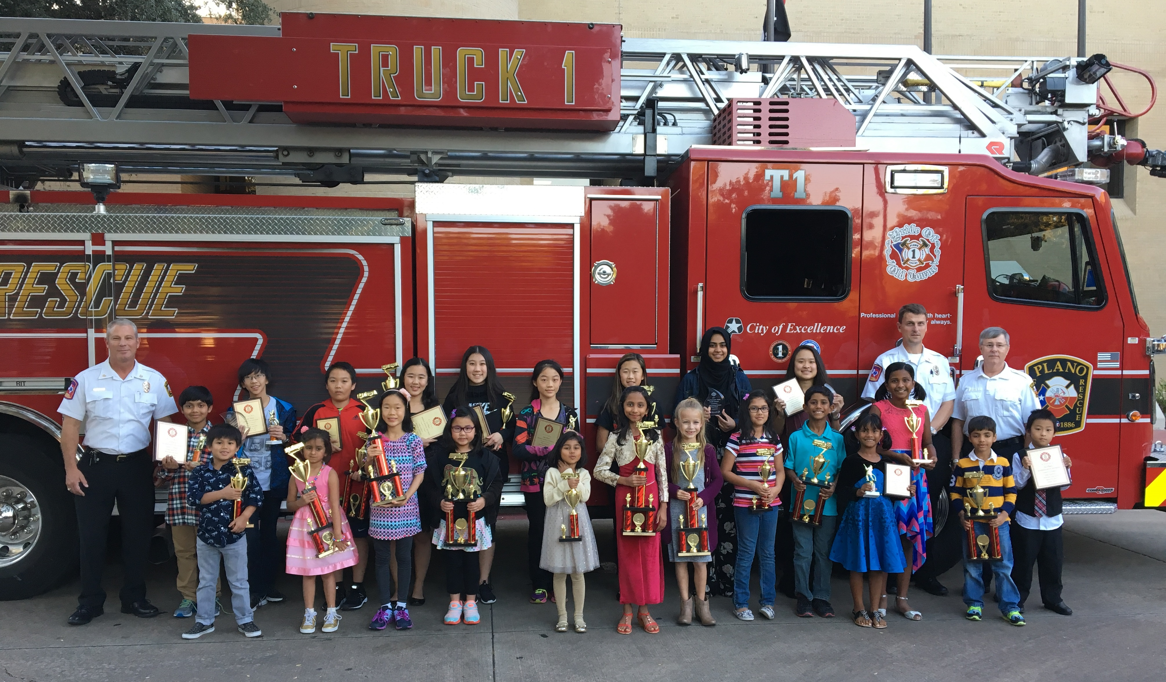 Group photo of winners with trophies and firetruck