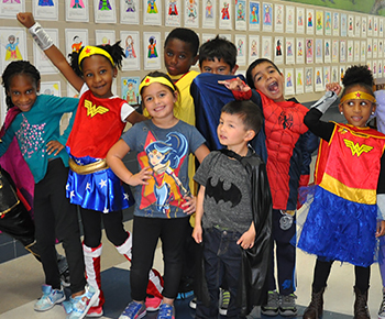 Several elementary students in superhero costumes