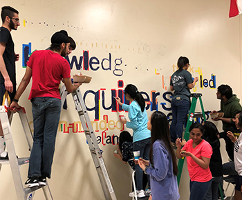 PESH IB Students painting mural at Huffman
