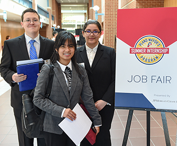Three students holding resumes at job fair
