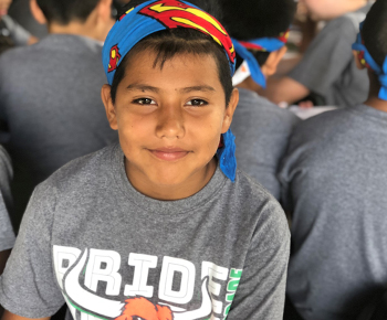 smiling Mendenhall camper student with bandana on head