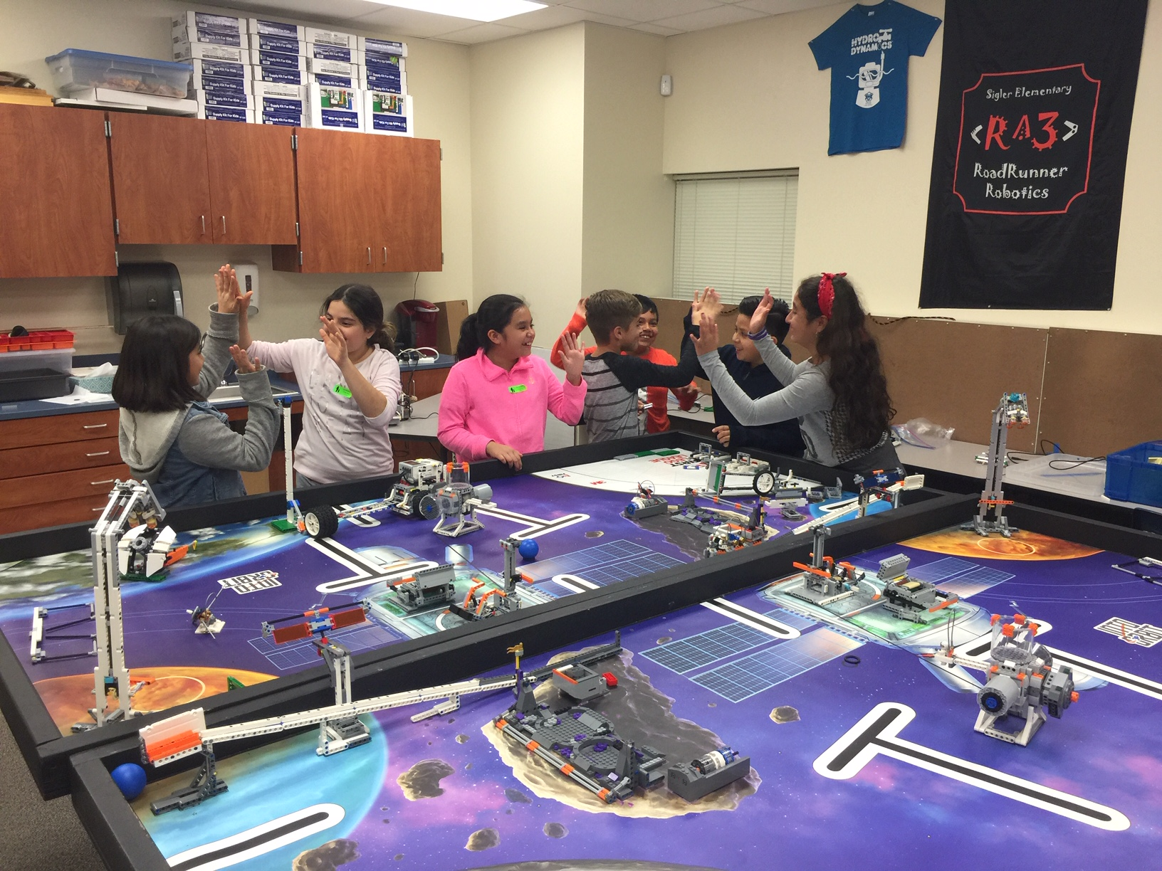 Sigler Elem, FLL robotics team celebrating with high fives