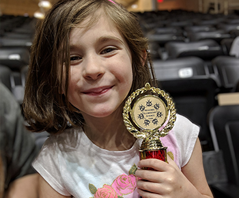 first grade girl with her first place trophy