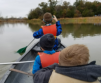 fifth grade campers paddling a canoe on pond