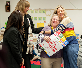 teacher receiving hug from principal