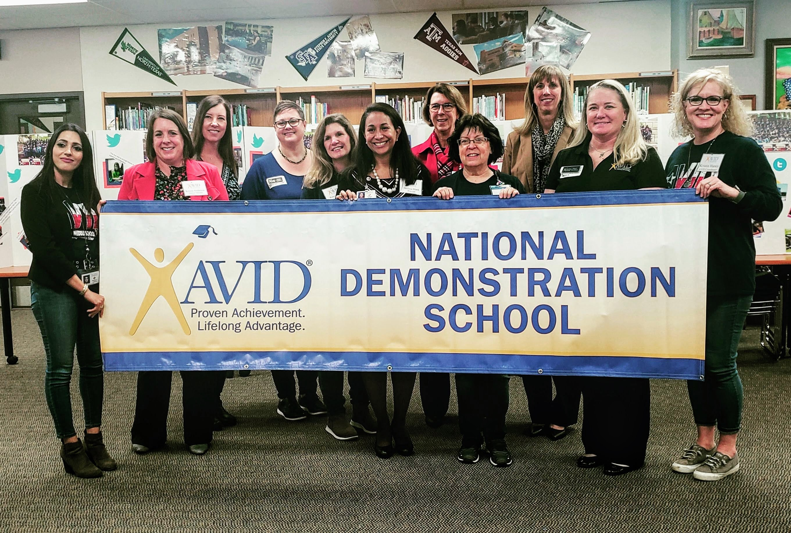 Armstrong staff holding AVID National Demonstration School banner