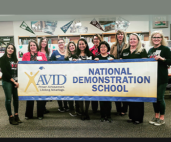 Armstrong and AVID staff with banner