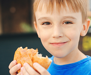 boy eating sandwich on a bun