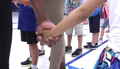Two children holding hands in the gym.