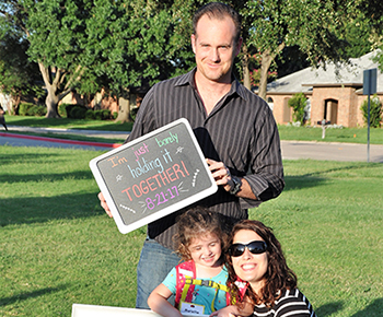 Family with welcome signs on the first day of school