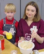 Preschool student aide making cookies with young child