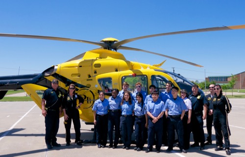 students and medical helicopter personnel in front of helicopter