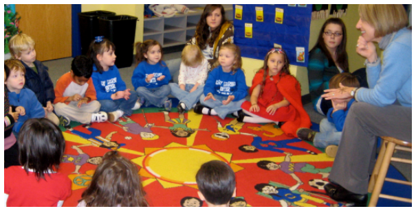 Preschool students with student aides at circle time