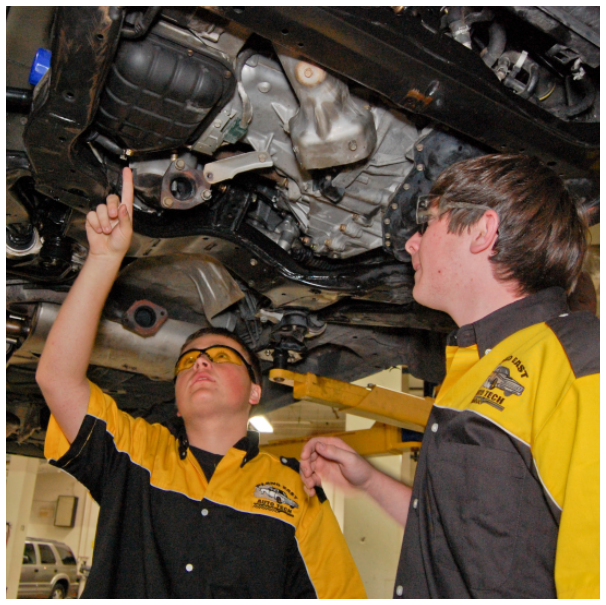 two students working on underside of car