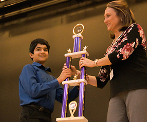 smiling science fair winner with giant trophy