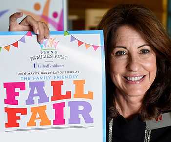 smiling woman with fall fair poster