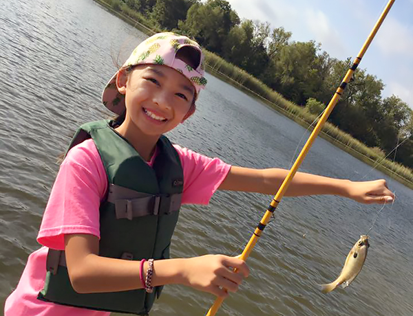 Rose Haggar Elementary Student with fishing pole and small blue gill fish.