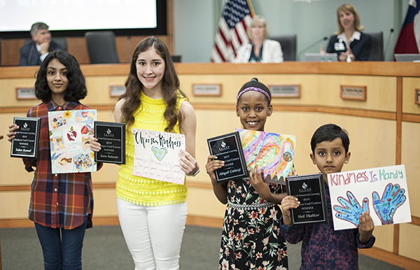 Kindness card winners with their artwork and plaques