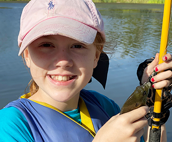 Elementary girl with fishing pole and a fish she caught at camp