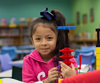 smiling girl building a structure