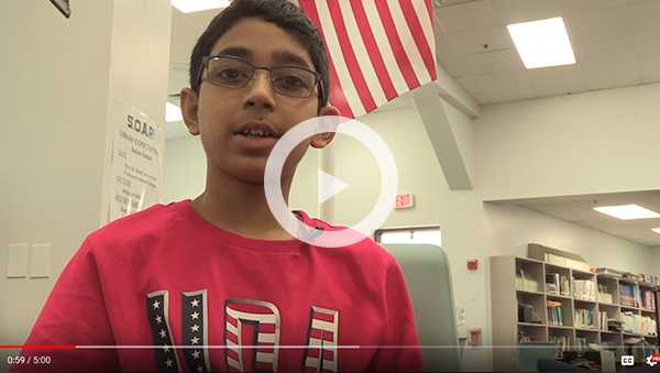 boy with glasses and USA t-shirt speaking to camera